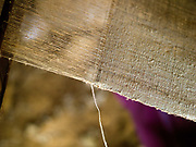 A close up of hemp fabric on a loom showing the warp and weft threads in the Hmong village of Ban Long Kuang, Houaphan province, Lao PDR. Hmong weavers in Houaphan province use a back strap loom where the tension of the warp is controlled by the weaver wearing a strap around their waist. Making hemp fabric is a long and laborious process; the end result is a strong durable cloth with qualities similar to linen which the Hmong women use to make their traditional clothing. In Lao PDR, hemp is now only cultivated in remote mountainous areas of the north.