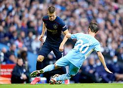 Burnley's Johann Berg Gudmundsson (left) and Manchester City's Bernardo Silva battle for the ball during the Premier League match at the Etihad Stadium, Manchester. Picture date: Saturday October 16, 2021.