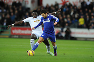Cesc Fabregas of Chelsea is fouled by Bafetimbi Gomis of Swansea city.  Barclays Premier League match, Swansea city v Chelsea at the Liberty Stadium in Swansea, South Wales on Saturday 17th Jan 2015.<br /> pic by Andrew Orchard, Andrew Orchard sports photography.