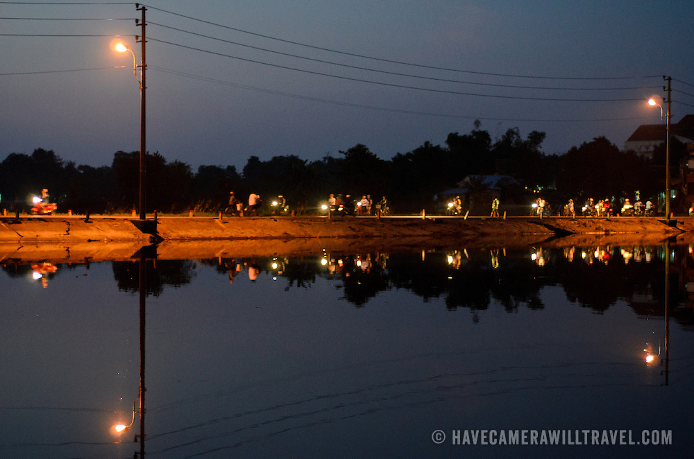 A low road forms a land bridge across a section of the Perfume River in Hue, Vietnam. The street is buzzing at dusk with locals crossing on their motorbikes, scooters, and bicycles.