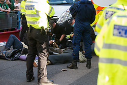 London, UK. 23rd August, 2021. Thames Valley Police officers work to remove Extinction Rebellion activists from a lock-on in St Martin's Lane during the first day of Impossible Rebellion protests. Extinction Rebellion are calling on the UK government to cease all new fossil fuel investment with immediate effect. Credit: Mark Kerrison/Alamy Live News