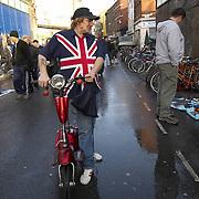 Man wearing a union jack shirt with a red moped, Brick Lane market, London