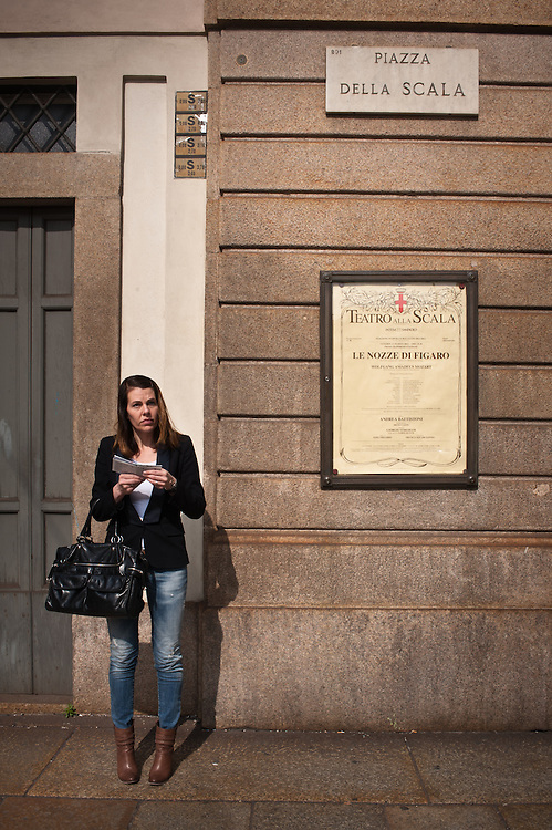 """MILAN, ITALY - MAR 23: a woman stands by """"The marriage of Figaro""""  playbill at Teatro alla Scala in Milan on March 23, 2012."""