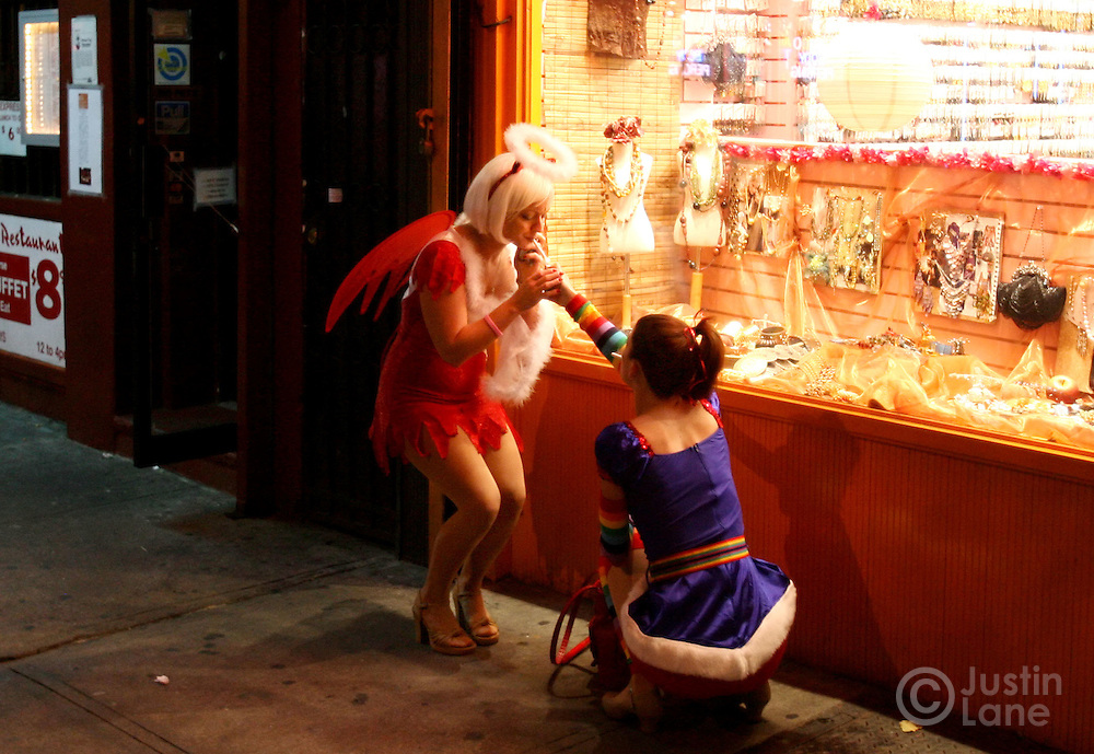 A woman dressed as an angel lights a cigarette in Greenwich Village during the annual Halloween parade 31 OCtober 2005.