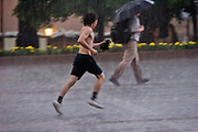 Moscow, Russia, 14/07/2006..People on Manezh Square by the Kremlin run for cover during a sudden summer thunderstorm.