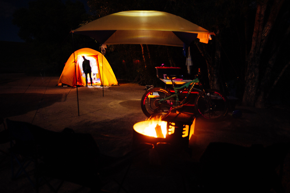 Heather Goodrich putting the kids to sleep at night in a campsite lit by fire.