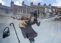 © Licensed to London News Pictures; 08/02/2021; Bristol, UK. A mural, 'Aachoo', by Banksy showing a woman coughing out her dentures on a wall in Vale Street during the Covid-19 coronavirus pandemic in England has now been completely enclosed with a box cover and screen which makes it hard to photograph without reflections, along with security measures including a CCTV camera and a notice of a smoke machine. A google list entry has been listed on Google as 'temporarily closed'. The house was in the process of being sold when the mural was painted on 10 December 2020. From social media it appears the protective measures were installed on 23 January 2021. With a roughly 22-degree gradient incline, Vale Street in the Totterdown area of Bristol is said to be England's steepest street. Photo credit: Simon Chapman/LNP.