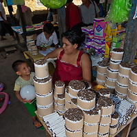 A young mother plays with her son between selling handmade cigarettes in an outdoor market in upper Belem, a crowded neighborhood in Iquitos, Peru.