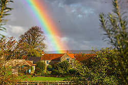 © Licensed to London News Pictures. 15/10/2020. Lockton UK. A rainbow falls on the picturesque village of Lockton in the North Yorkshire Moors this morning after a spell of heavy rain. Photo credit: Andrew McCaren/LNP