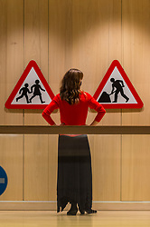 "© Licensed to London News Pictures. 20/10/2020. LONDON, UK.  London, UK.  20 October 2020. A staff member views ""Children"" and ""Road Works"" road signs by Margaret Calvert.  Preview of Margaret Calvert: Woman at Work at the Design Museum in Kensington.  The exhibition explores the graphic designer's influence on the UK's visual identity and continuing impact through projects such as the new Rail Alphabet 2 typeface for Network Rail.  Photo credit: Stephen Chung/LNP"