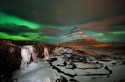 Aurora Borealis, the Northern Lights, over the Kirkjufellsfoss waterfall and Kirkjufell, a 463 metre mountain on the west coast of Iceland.
