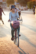 A young woman cycling through the streets of Siem Reap, Cambodia