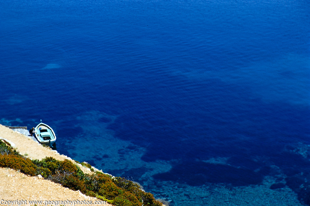 Looking down on small open boat moored on coast of deep blue sea, island of Ibiza, Balearic Islands, Spain, 1950s