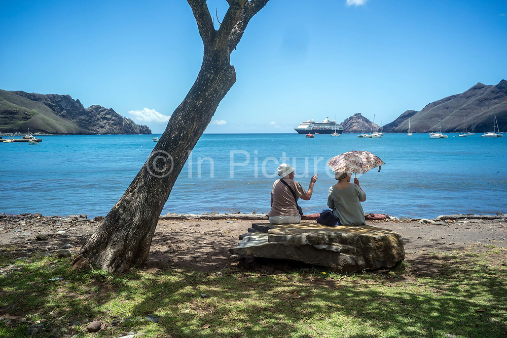 Two elderly women tourists disembarked from a cruise ship chat on the promenade of Taiohae Bay on the island of Nuku Hiva, Marquesan Islands, French Polynesia.