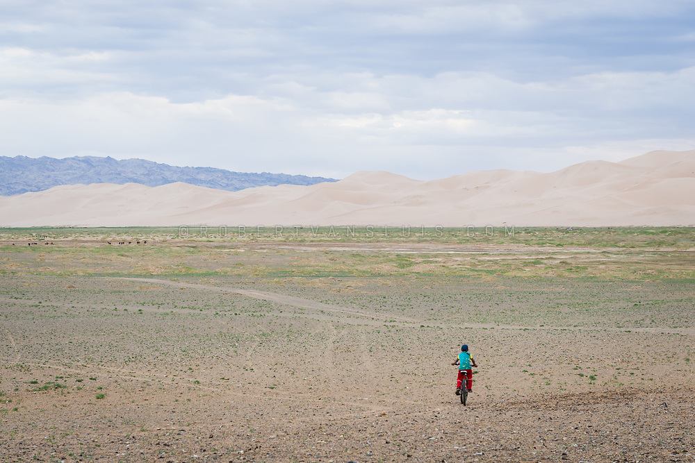 A boy cycles off into the Gobi Desert near the Khongoryn Sand Dunes, Mongolia. Photo ©Robert van Sluis - www.robertvansluis.com