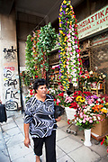 Woman walks past a shop selling plastic flowers in Psiri. Athens is the capital and largest city of Greece. It dominates the Attica periphery and is one of the world's oldest cities, as its recorded history spans around 3,400 years. Classical Athens was a powerful city-state. A centre for the arts, learning and philosophy.