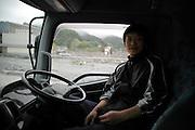 Onagawa - Keita HORIMURA - juin 2011<br /> Keita Horimura m'emmène dans son camion benne chargé de débris d'architectures pour quelques kilomètres de traversée de l'ancienne ville. Le 11 mars, il prit sa fille à lécole et se réfugia sur les crêtes. Étant bloqué et n'ayant plus de lieu où rester, ils passèrent la nuit dans la voiture. Aujourdhui il vit hébergé dans sa famille en dehors de la ville. .Lorsque nous arrivons au front de mer, Il me montre une carcasse déformée, anciennement sa maison. Il fait face à sa condition en disant que rien ne peut plus être changé et quil faut avancer. En me quittant il lance à nouveau un message d'espoir disant que le Japon et les Japonais sont fort et se relèveront : Gambate Nippon ! (Courage Japon !)