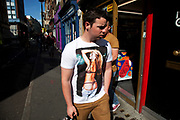 Man wearing a t-shirt depicting a scantily clad woman. Seemingly a bizarre thing to wear the model printed on the shirt, wearing underwear and baring herself is perhaps some kind of fashion or style statement, however odd it seems. Berwick Street, Soho, London, UK.