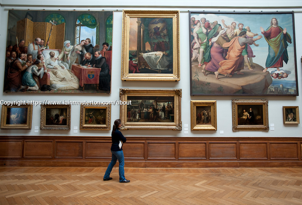 Visitor looking at paintings at Royal Museum for Fine Arts in Antwerp Belgium