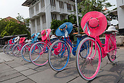 Brightly coloured pink and blue Dutch bicycles with lacy hats at Fatahillah Square in Jakarta on the 1st November 2019 in Java in Indonesia.
