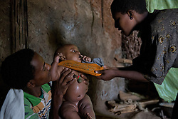 Fifteen-year-old Destaye and her husband, Addisu, 27, dress their son in their home near Bahir Dar, Ethiopia on Aug. 12, 2012. The couple divide their time between working in the fields and taking care of their 6-month-old baby. Like many other young couples, they tend to the domestic, economic and personal demands of being young parents. At the time of their marriage, when Destaye was age 11, she was still in school and her husband expressed interest in letting her continue her education. Since the birth of their son, however, she has had to confine her life exclusively to being a wife and mother.