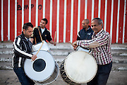 """Father Abdush (right) and his sons Mersid (2nd left), Erdal ( left) and Ergul (2nd right) during a drum session on a stage in front of the """"House of Culture"""" in Delcevo, Macedonia. The Roma family - father and his 3 sons - are well know for their drum perfomances and also they build their drums themselves."""