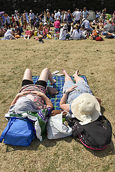 July 6, 2018 - London, UK - LONDON, UK. Spectators sunbathe whilst queuing for day tickets in Wimbledon Park to the Wimbledon Tennis Championships.  Temperatures forecast to approach 30C mean that the majority have taken precautions to protect themselves from the sun by wearing sunglasses and sunhats. (Credit Image: © Stephen Chung/London News Pictures via ZUMA Wire)