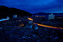 Cars make their way through in deserted town devastated by tsunami in Otsuchi, Iwate prefecture, Japan, April 4, 2011. Thousands of Japanese and American military personnel joined together Friday in a final three-day sweep to search for those still missing from last month's massive earthquake and tsunami.