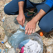 A Syrian refugee waging his clothes in two cut water containers outside Kara Tepe camp.