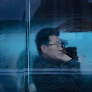 A man is looking through the window of a bus.Commuting can be very time consuming in Pyongyang as there are not lot of buses. Long queues are forming and buses are overcrowded.