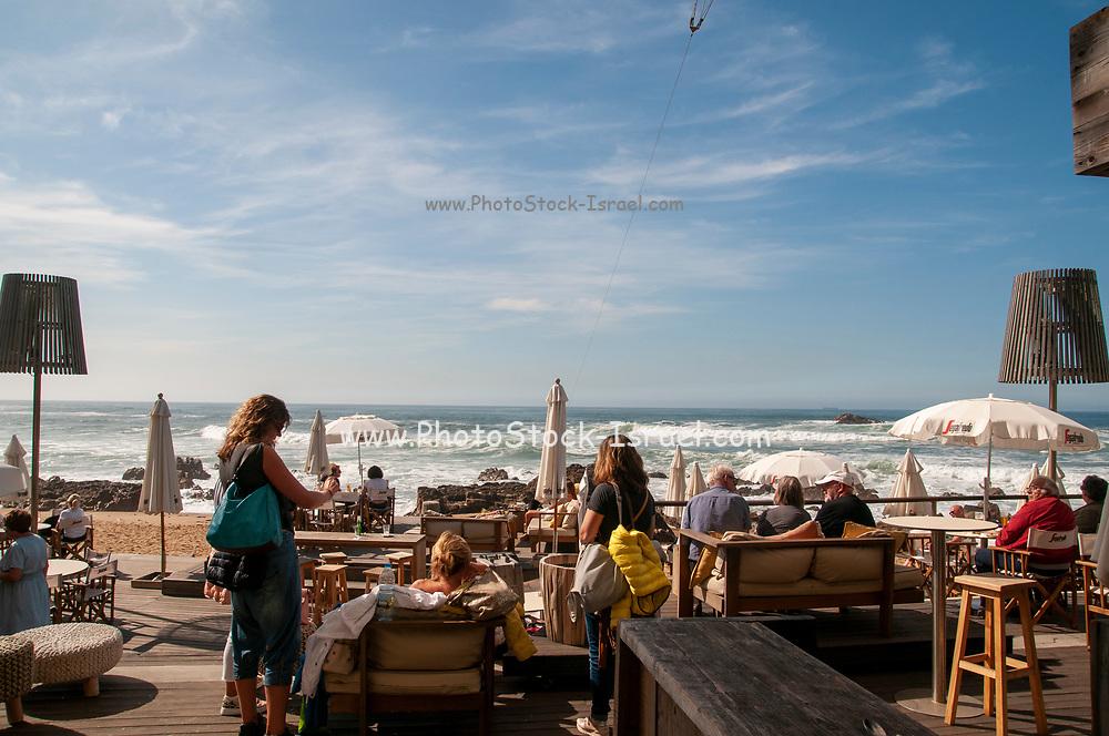 Open air cafe on the Atlantic Ocean photographed at the Douro River estuary (Foz do Douro). Porto, Portugal
