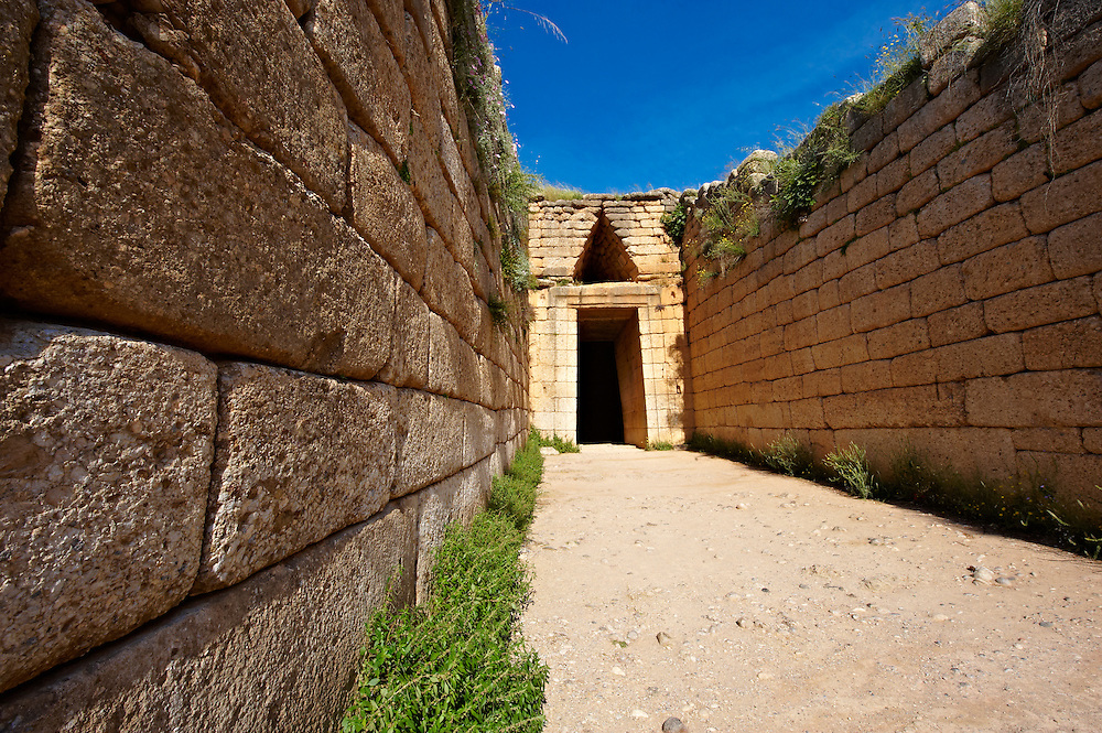 """Entrance to the Treasury of Atreus is an impressive """"tholos"""" beehive shaped tomb on the Panagitsa Hill at Mycenae. The entrance has the typical square 2 upright jams covered with a lintel that weigts around 100 tons. Above the door is a trangular """"False"""" or corbel arch.  Mycenae UNESCO World Heritage  Archaeological Site, Peloponnese, Greece . <br /> <br /> Visit our MYCENAEN ART PHOTO COLLECTIONS for more photos to download  as wall art prints https://funkystock.photoshelter.com/gallery-collection/Pictures-Images-of-Ancient-Mycenaean-Art-Artefacts-Archaeology-Sites/C0000xRC5WLQcbhQ<br /> .<br /> <br /> Visit our GREEK HISTORIC PLACES PHOTO COLLECTIONS for more photos to download or buy as wall art prints https://funkystock.photoshelter.com/gallery-collection/Pictures-Images-of-Greece-Photos-of-Greek-Historic-Landmark-Sites/C0000w6e8OkknEb8"""