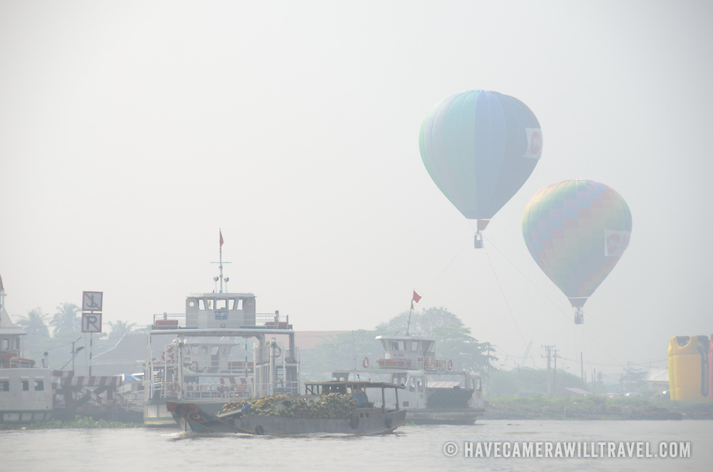 Two hot air balloons float in the air about several ships on the Saigon River in Ho Chi Minh City, Vietnam.