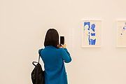 New York, NY - May 3, 2019. A woman at the Frieze Art Fair on New York City's Randalls Island takes a photo of Lisa Brice's gouache at the Salon 94 gallery.