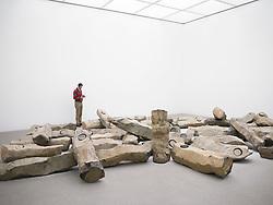 Visitor looking at sculpture Das  Ende des 20 Jahrhunderts by Joseph Beuys at Pinakothek Moderne art museum in Munich Germany
