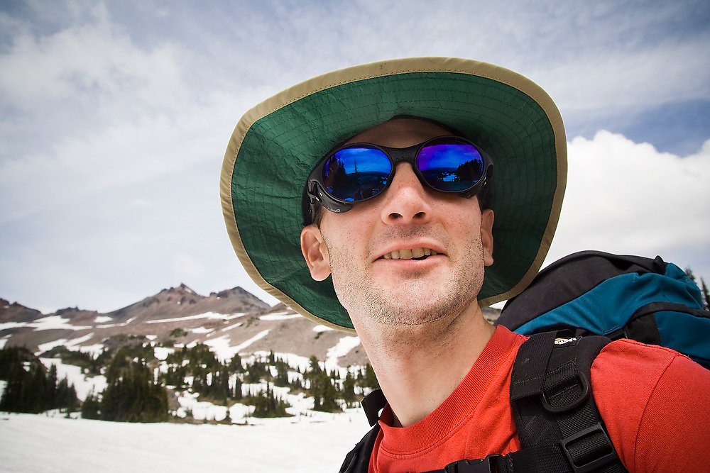 Dallas Anderson wears glacier sunglasses and a wide brimmed hat on a backpacking trip to Goat Lake in Goat Rocks Wilderness, Washington.