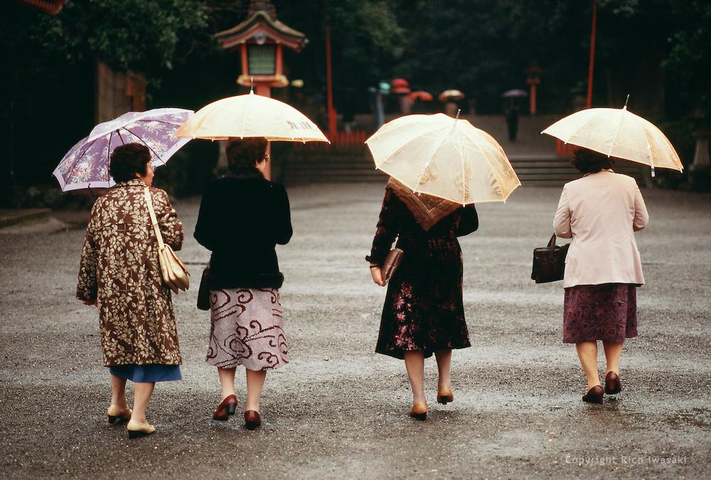 Four women with umbrellas visit a shrine in rainy weather, Miyazaki, Miyazaki Prefecture, Japan