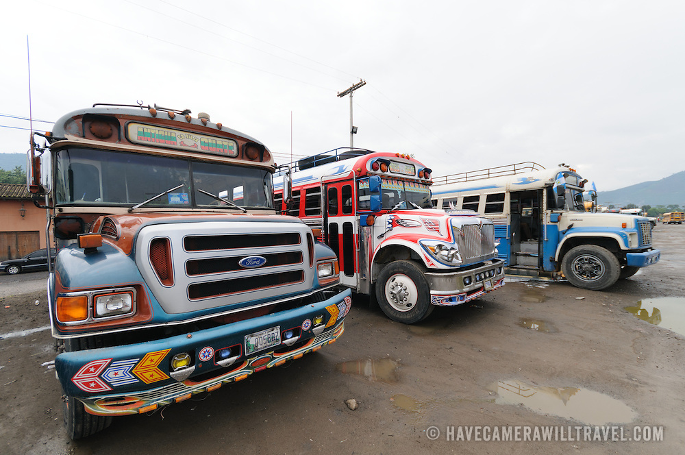 Brightly painted chicken buses behind the Mercado Municipal (town market) in Antigua, Guatemala. From this extensive central bus interchange the routes radiate out across Guatemala. Often brightly painted, the chicken buses are retrofitted American school buses and provide a cheap mode of transport throughout the country.