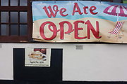 With a picture of a £2.95 slice of apple pie underneath, a banner tells customers that a seedy cafe is still open, on 17th September 2016, on the Western Esplanade, at Southend, Essex, England. Southend-on-Sea is a seaside town on the north side of the Thames estuary 40 miles 64 km east of central London. In its heyday, the working class visited from the capital when train transport allowed them to enjoy its beaches and the worlds longest pier. Its splendour faded on the advent of package holidays to Spain etc.