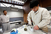 Isao Sanno (left) watches Shuhei Suzuki (right) prepare a food sample at the Becquerel Centre in a farmers' market in Miharu, where locally grown food is tested for nuclear contamination. Miharu, Fukushima, Japan. Friday May 4th 2012