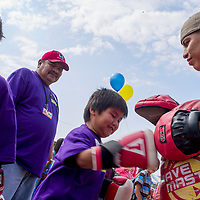 Harlen James practices punching a bag held by Jeremiah Bahe from Bahe Boxing during the Ashkii Happy Kids Day event at the Navajo Nation Fair in Window Rock Thursday.
