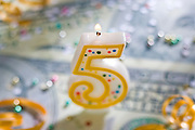 A 5 year celebration candle on U.S. currency.