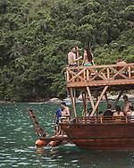 Paraty, Brazil - March 17, 2019: Passengers enjoy a boat tour taking them on a popular day trip to several beaches near Paraty, Rio de Janeiro State, Brazil.