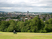 A woman sits on a bench over looking the city at Meersbrook Park on 25 June 2017 in Sheffield, United Kingdom