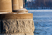 Bridge footings hold the roadbed above the Mississipi River. Ice partially covers the river channel.
