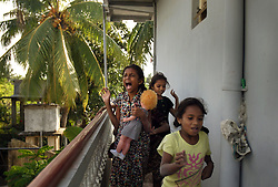 "Brianna Barthelot, 13, holding doll, and her sister Shrianna Barthelot, 11, back right, play ""tsunami"" with friends, Batticaloa, Sri Lanka, Jan. 28, 2005. The sisters lost both parents and their older brother in the tsunami. They are now living with relatives at night and spending most of their days at the convent where the rest of their village is staying. Residents of the small Christian village Dutch Bar spent more than six weeks in a makeshift refugee camp at the local convent recovering from the devastating tsunami that hit the eastern and southern borders of Sri Lanka. They were then moved into another temporary living camp, while awaiting the building of new homes. More than 150 members in this community of less than 1000 people died in the tragic event."
