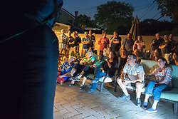 June 11, 2017 - Merrick, New York, United States - 'American Grit' TV contestant CHRIS EDOM (lower right, wearing white GOT GRIT? T-shirt), 48, sits next to his wife JOAN EDOM, both of Merrick, as they host backyard Viewing Party for Season 2 premiere. Edom family relatives and neighbors watched Episode 1 of FOX network reality television series on very large screen that Sunday night outdoors. (Credit Image: © Ann Parry via ZUMA Wire)