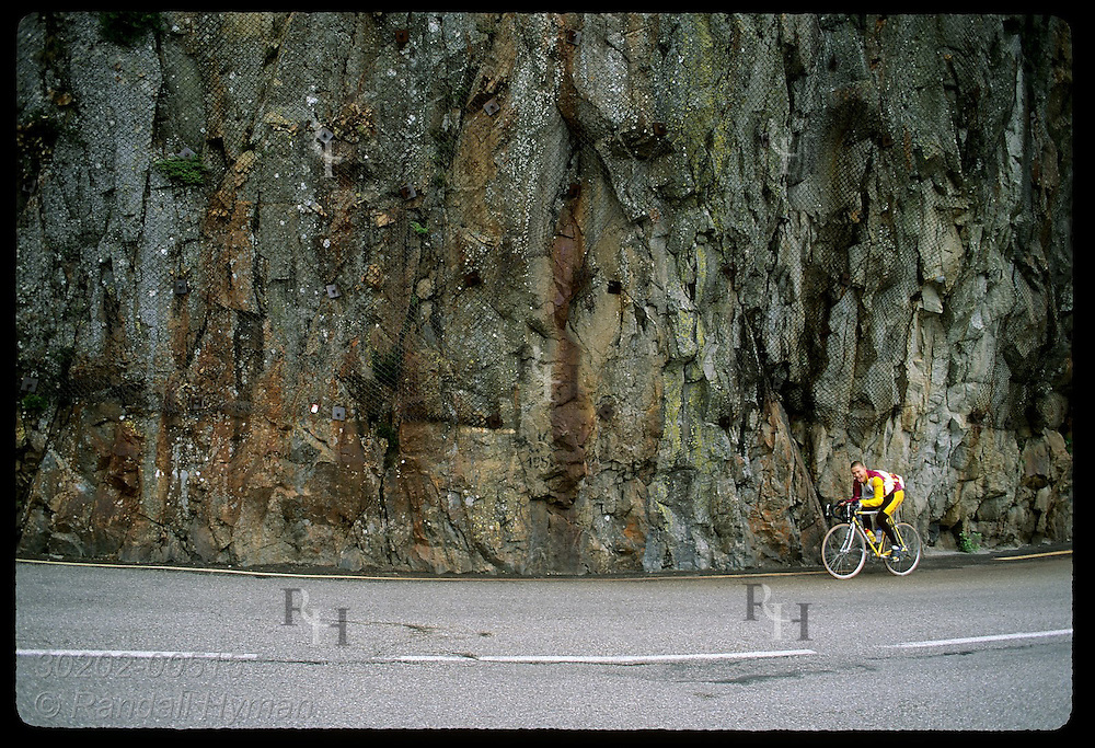 Cyclist pedals past rock face on road to Col de la Schlucht pass in the Vosges Mtns; Alsace. France