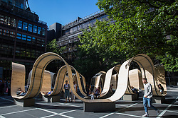London, UK. 13 September, 2019. Office workers and passersby enjoy Paul Cocksedge's Please Be Seated installation in Finsbury Square Avenue in the heart of Broadgate as a Landmark Project for the London Design Festival. Made from scaffolding planks in collaboration with Essex interiors company White & White, the installation features curves for people to sit on and walk under and is intended to respond to the changing rhythm of the community, so enhancing London's largest pedestrianised neighbourhood.