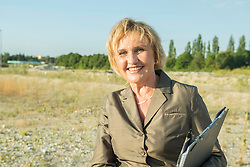 Smiling mature woman with clipboard at development area